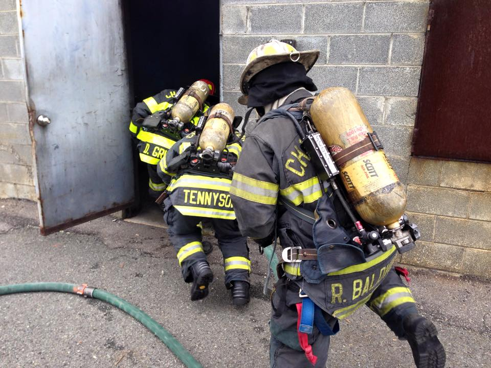 Firefighters Crouching Entering a Building During Training